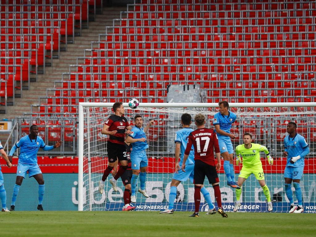 Nuremberg's Austrian defender Georg Margreitter (Up L) scores the 1-0 during the German second division Bundesliga football match 1 FC Nuernberg vs VfL Bochum in Nuremberg, on May 16, 2021. (Photo by Kai PFAFFENBACH / POOL / AFP) / DFL REGULATIONS PROHIBIT ANY USE OF PHOTOGRAPHS AS IMAGE SEQUENCES AND/OR QUASI-VIDEO