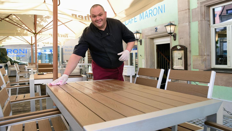 Im Biergarten des Café Maroni sind die Tische ausgedünnt, Koch Blagovest legt letzte Hand an, damit sich heute Gäste am Zirndorfer Marktplatz niederlassen können.