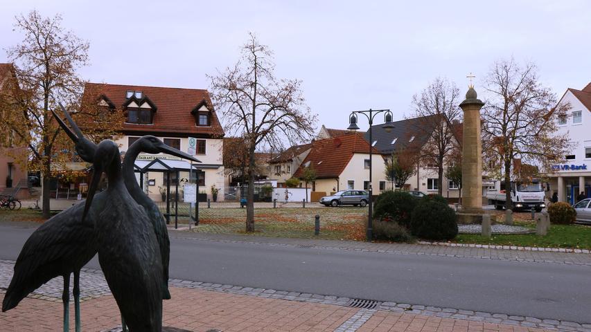 Der Marktplatz mit Storchen-Skulptur.