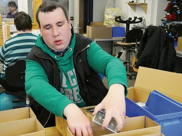 Ein Beschäftigter der Diakoneo-Werkstatt Laubenzedel beim Verpacken von Fertigungsteilen