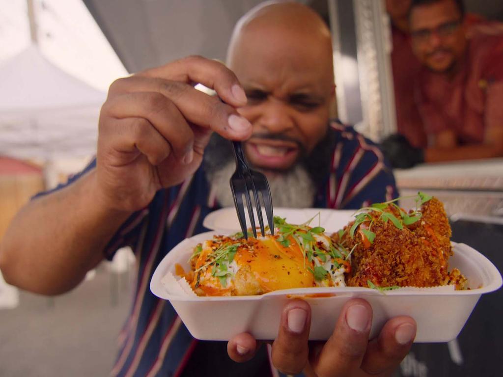 "Fresh, Fried & Crispy: Season 1. Episode 3, ""Las Vegas""Pictured: Daymon Scott ""Daym Drops"" Patterson (Food Critic) tasting the Hakka Street Noddles (pork tonkatsu, shrimp and fried egg) by chef Manny Rivera (chef/ co-owner) of Prisma. c. Courtesy of Netflix © 2021"