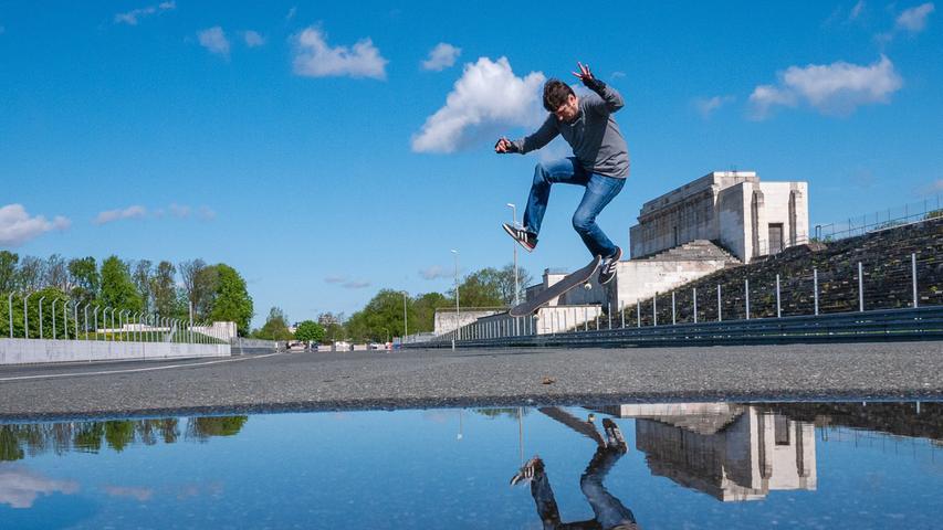 Am Rande einer Pfütze vor der Steintribüne zeigt ein Skater sein Können - an einer Wasserlandung ist er knapp vorbei geschrammt.