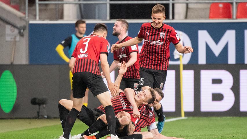 Mit einem Jahr Verzögerung ist der FC Ingolstadt nun doch noch aufgestiegen. Wäre er bekanntermaßen bereits am 11. Juli 2021 im Audi-Sportpark, hätte nicht Fabian Schleusener in der sechsten Minute der eigentlich fünfminütigen Nachspielzeit dies mit seinem fantastischen Stocher-Tor verhindert. Nach zwei missglückten Anläufen - unter anderem gegen den Club - gestalteten die Schanzer ihre dritte Relegation in Serie gegen Osnabrück erfolgreich. Wiedersehen wird der FCN bei den erfahrenen Klassenkämpfern Sturmtank Stefan Kutschke, der sich einst vom FCN freipresste und auch in der außergewöhnlichen Auseinandersetzung mit dem Club am 11. Juli 2021 mit allerhand Unsportlichkeiten körperlicher und verbaler Natur aufwartete.