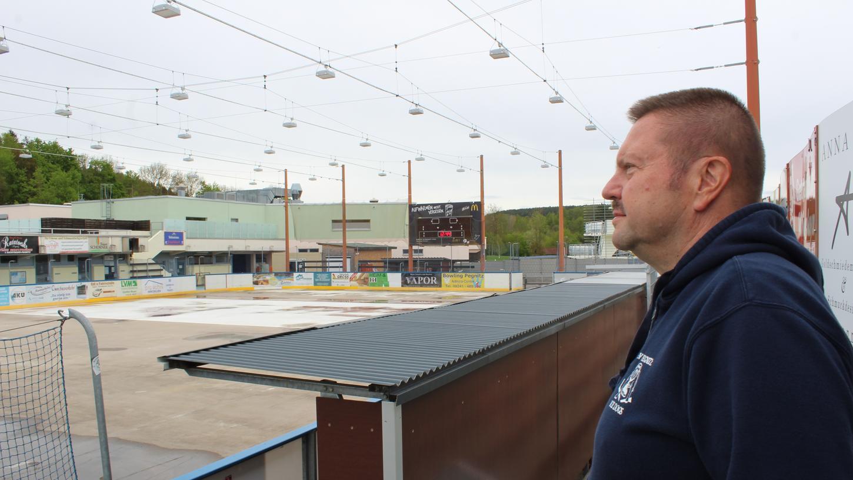 Mit ein bisschen Wehmut blickt Ralf Putzin von seinem alten Stammplatz auf die leere Eisfläche - die Spielerbänke versperren ihm dort nun die Sicht.