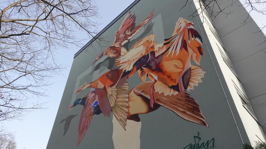"""Mit """"Wurzeln und Flügel"""" spielt Julian Vogel nicht nur auf Goethe an, sondern auch auf ein Kunstwerk im Stadtteil. Die """"Allegorie des Wassers"""", welches aus mehreren Skulpturen besteht, die durch einen fiktiven Bach miteinander verbunden sind, wurde 1971 von einer japanischen Künstler:innengruppe in Langwasser installiert. Julian Vogel greift diese Skulpturen in seinem Bild auf und erweckt sie zu neuem Leben, indem er Enten daraus emporsteigen lässt. Wichtig ist es dem Künstler, die Eichen vor dem Mural als Teil des Werkes zu verstehen und die fliegenden Enten ganz bewusst durch deren Äste zu betrachten"""