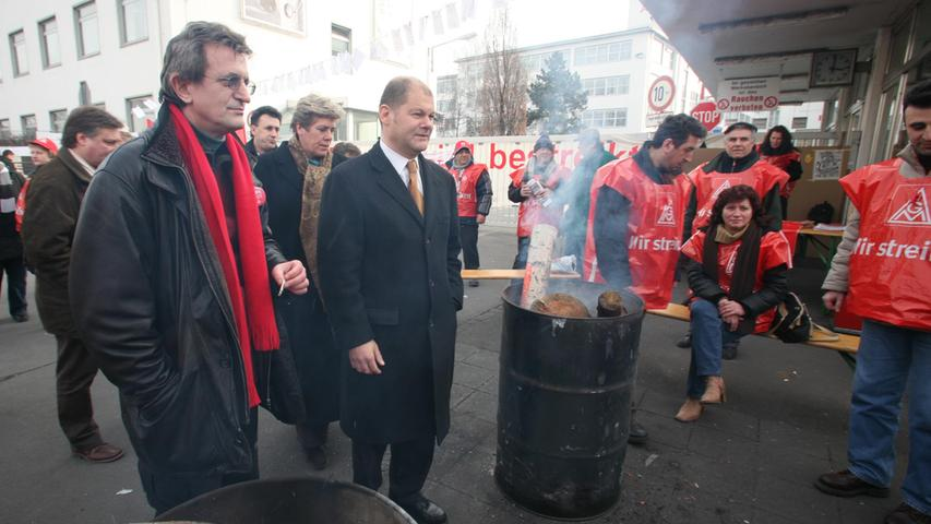 Von 2007 bis 2009 bekleidete Olaf Scholzdas Amt des Bundesministers für Arbeit und Soziales in der Großen Koalition unter Bundeskanzlerin Angela Merkel. Er folgte auf ParteigenosseFranz Müntefering, der sich aus familiären Gründen aus dem Amt zurückzog. Hier besuchte er den AEG-Streik in Nürnberg mit Lizzy Gröhner und Martin Burkert.