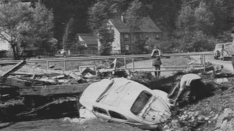 Zwei Feuerwehrleute konnten sich mit Mühe aus diesem Wagen retten, der im Hirschbachtal von der Flut mit großer Gewalt an eine Brücke geschwemmt worden war. Das Bild gibt einen Eindruck von den schweren Zerstörungen in dem beliebten Ausflugsgebiet.