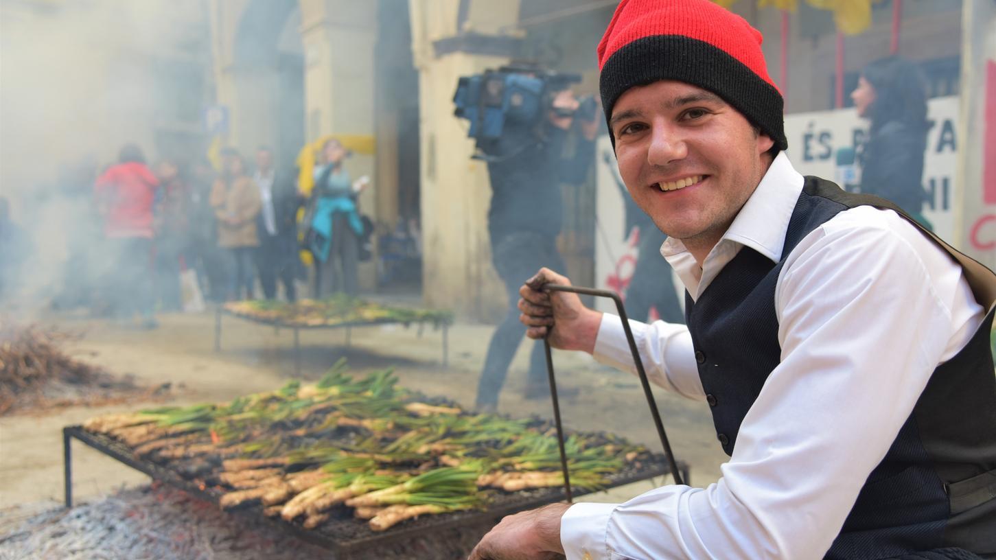 Katalonischer Lauchbub: Junger Mann am Grill beim traditionellen Fest der Frühlingszwiebel.