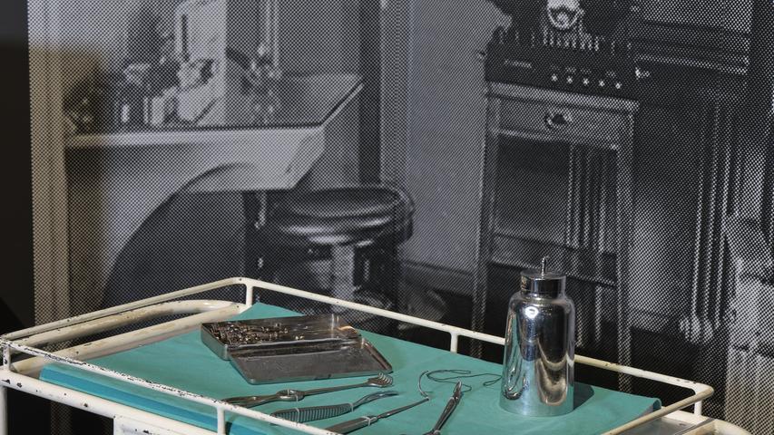 Blick auf einen Rollwagen mit Operationsbesteck und –utensilien, um 1930.
