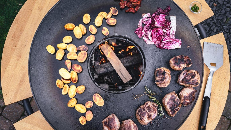 Mit einer Feuerplatte macht Grillen gleich noch mehr Spaß. Um den Aufsatz für Kugelgrills oder Feuertonnen stehen mehrere Köche und können sich so während des Zubereitens unterhalten, ähnlich wie beim Raclette.