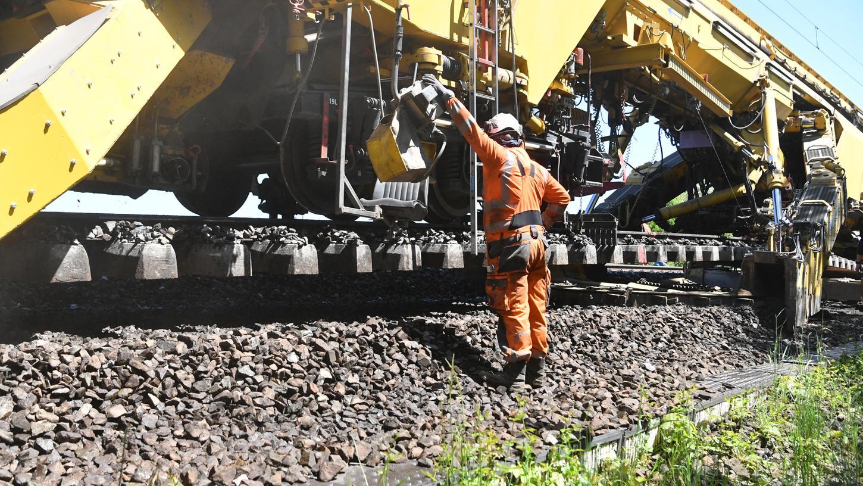 Die Arbeiter überwachen, dass Katharina die Große auch sorgfältig arbeitet. Wenn sie mit der Arbeit fertig ist, kommt ein Schienenlegezug zum Einsatz, der dann Schwellen und Schienen austauschen wird.