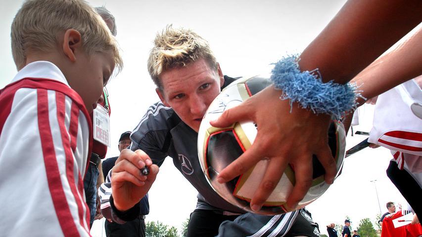 2005: Sebastian Schweinsteiger signiert bei einem öffentlichen Training einen Ball.