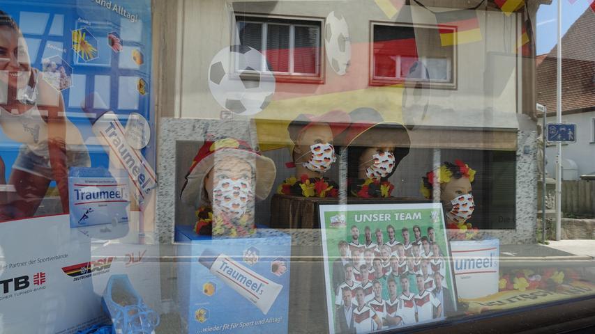 EM-Vorfreude in Pandemiezeiten: Apotheker und Fußballfan Georgios Halkias dekorierte sein Schaufenster mit schwarz-rot-goldenen Akzenten und Corona-Masken.