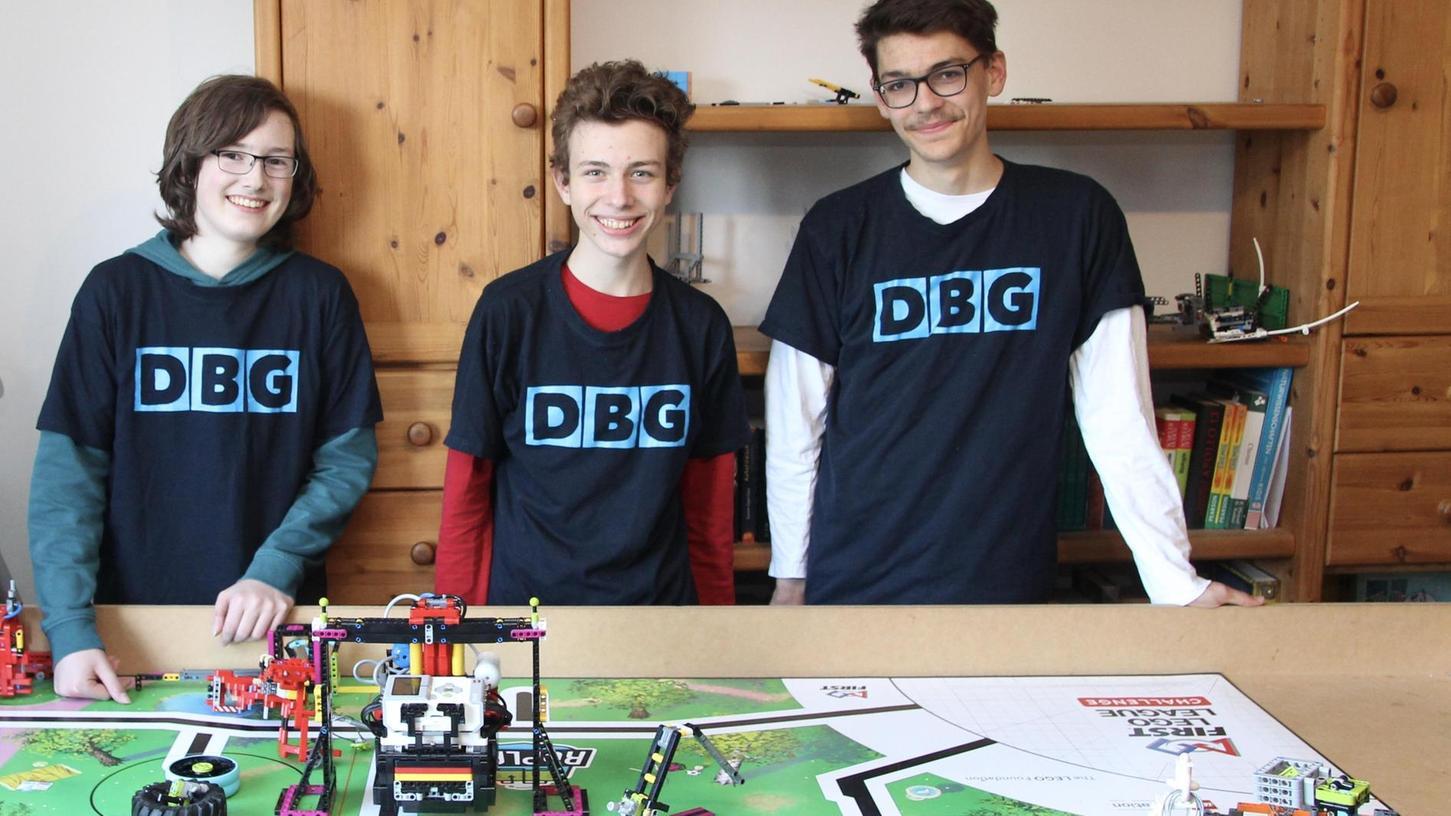 Die erfolgreichen Programmierer aus Oberasbach (v. li.): Anton, Stefan und Florian mit ihrem Roboter, der gerade einen Klimmzug macht.