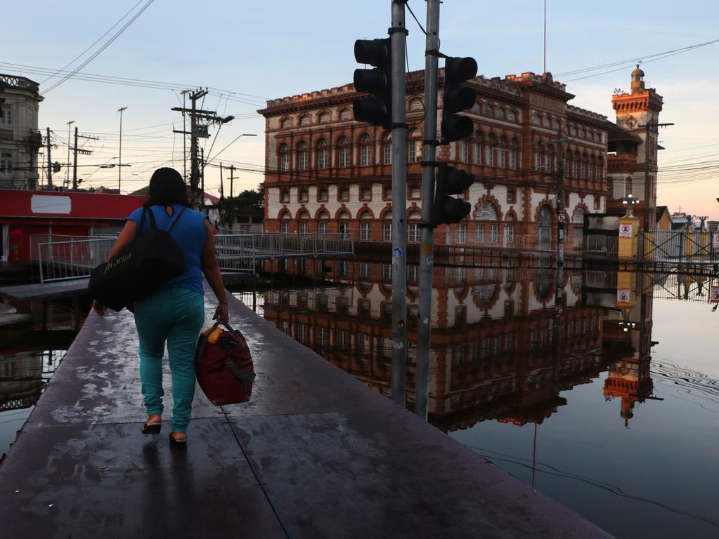 01.06.2021, Brasilien, Manaus: Eine Frau geht auf einem hölzernen Steg über eine Straße, die vom Fluss Negro überflutet wurde, in Manaus. Die Flüsse rund um Brasiliens größte Stadt im Amazonas-Regenwald sind auf ein Niveau angeschwollen, das seit mehr als einem Jahrhundert der Aufzeichnungen nicht mehr erreicht wurde, so die am Dienstag veröffentlichten Daten der Hafenbehörden von Manaus. Foto: Edmar Barros/AP/dpa +++ dpa-Bildfunk +++
