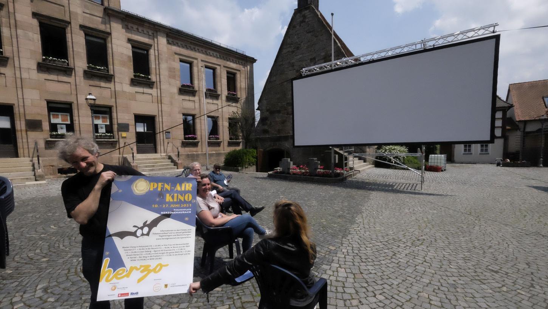 Wolfgang Meyer von mobileskino.de zeigt das neue Open-Air-Kinoplakat. Die Leinwand ist schon aufgebaut.