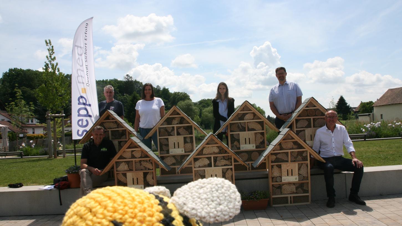Das symbolische Bienchen im Vordergrund freut sich schon auf die neuen Insektenhotels, die Florian Prester (stehend rechts) an die Vertreterinnen und Vertreter verschiedener Einrichtungen übergeben hat.