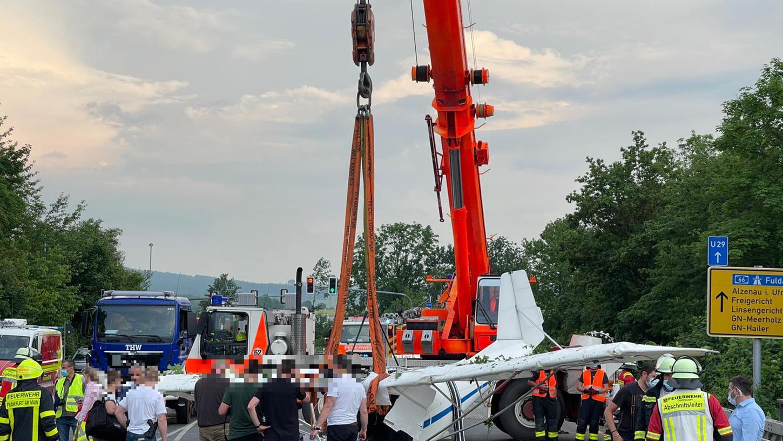 Einsatzkräfte der Feuerwehr haben mit Hilfe eines Krans das Wrack eines abgestürzten Kleinflugzeugs aus der Böschung einer Straße geborgen.