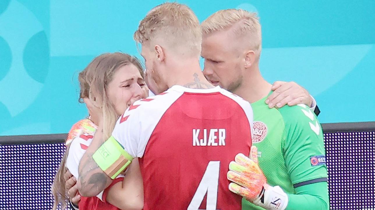 Ein Bild, das kaum zu ertragen ist: Während die Freundin von Christian Eriksen um dessen Leben bangt, versucht Ex-Bundesliga-Profi Simon Kjaer, ihr irgendwie seelisch beistehen zu können.