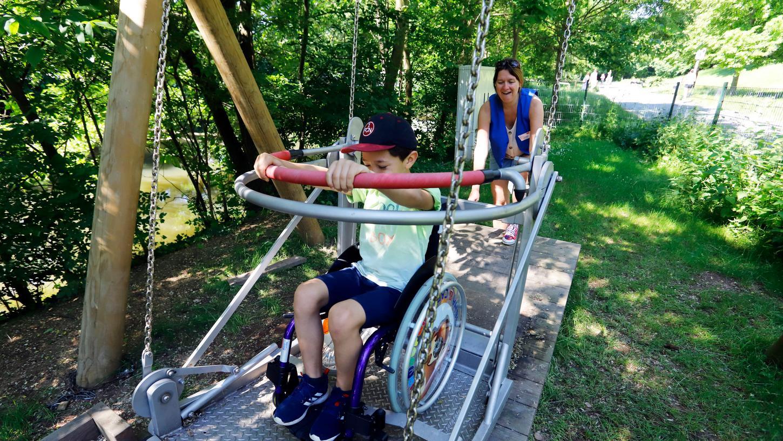 Neu auf dem Erfahrungsfeld: die Rolli-Schaukel. Der achtjährige Elias sitzt zum ersten Mal im Rollstuhl, Susanne Schuh vom Erfahrungsfeld schubst ihn an.