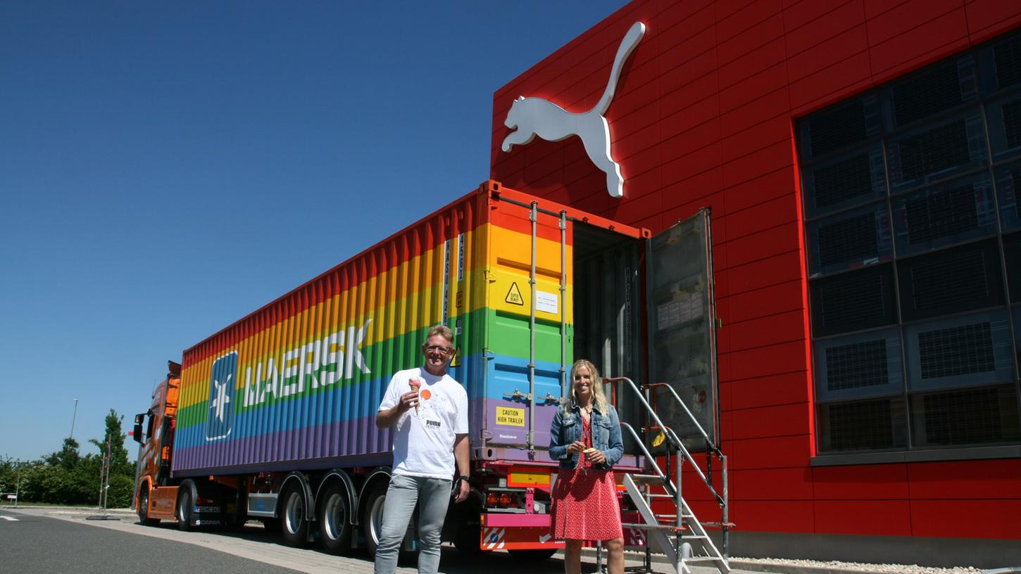 Die Puma-Mitarbeiter Katharina Redelberger und Dietmar Knöß lassen sichvor dem Regenbogen-Container am Puma Store in Herzogenaurach ein buntes Eis schmecken.
