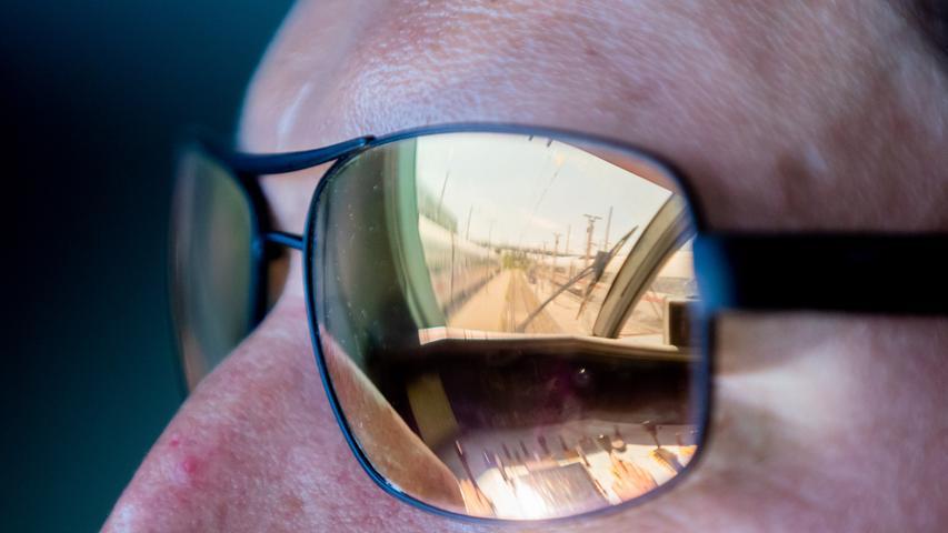 Der Führerstand eines ICE 2 spiegelt sich in der Sonnenbrille von Kevin Tinney, Ausbilder für Lokführer bei der Deutschen Bahn, als dieser den Zug ins ICE-Werk Rummelsburg fährt.