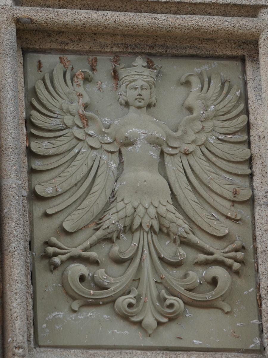 An der Front des Pfarrhauses kann man zwischen dem Sandstein diese weibliche Mischfigur entdecken.