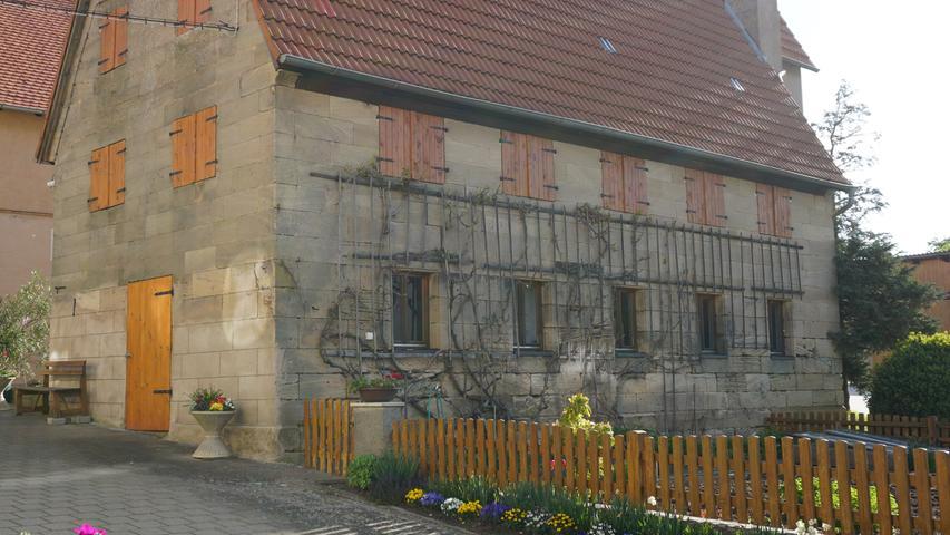 Das Dorfbild entlang der Hauptstraße ist geprägt durch zahlreiche Sandsteingebäude, wie diese liebevoll renovierte Scheune mit Gemüsegarten zeigt.