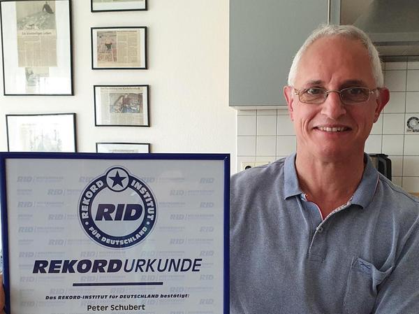 Peter Schubert aus Hallerndorf hält das offizielle Dokument, das seinen Rekordstatus bestätigt, in die Kamera.