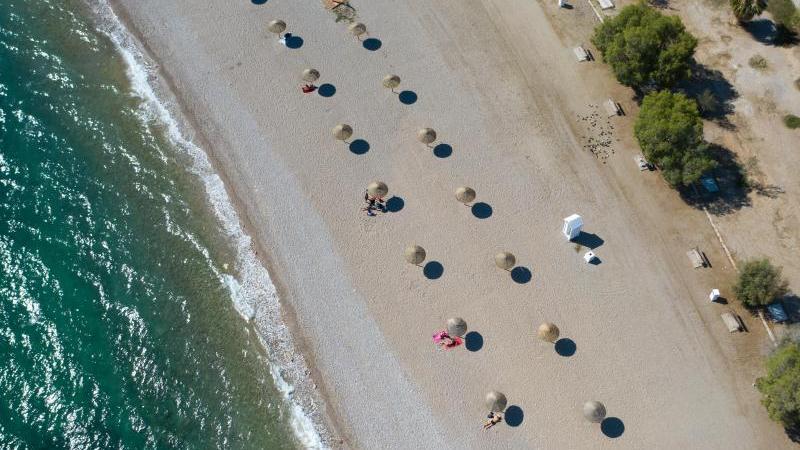 An einem Strand südlich von Athen stehen Sonnenschirme für Strandbesucher bereit. Wegen sinkender Corona-Infektionszahlen streicht die Bundesregierung am Sonntag Griechenland, fast ganz Frankreich, die Schweiz und Belgien von der Liste der Risikogebiete.