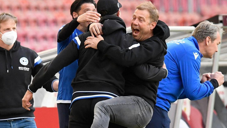 Nach dem Abpfiff brechen alle Dämme: Trainer Frank Kramer (graue Jeans) umarmt jeden, der ihm an der Seitenlinie in die Quere kommt, da mit dem 2:0 gegen den VfB Stuttgart Platz 15 und somit der direkte Klassenerhalt feststeht.