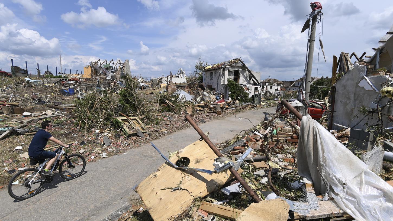 Ein Mann fährt mit seinem Fahrrad auf einerStraße vorbei an den Trümmern zerstörter und stark beschädigterGebäude im tschechischen Dorf Mikulcice.