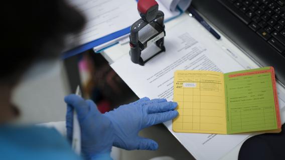 Ein Aufkleber, ein Stempel eine Unterschrift - mehr braucht es in den gelben Heften nicht, um eine Corona-Impfung zu dokumentieren.