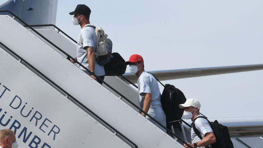(L-R) Germany midfielder Joshua Kimmich, forward Thomas Mueller and defender Robin Gosens board a plane at Nuremberg Airport, on June 28, 2021, as Germany's team travel to the United Kingdom on the eve of their UEFA EURO 2020 football match against England, played at Wembley Stadium in London. (Photo by Christof STACHE / AFP)
