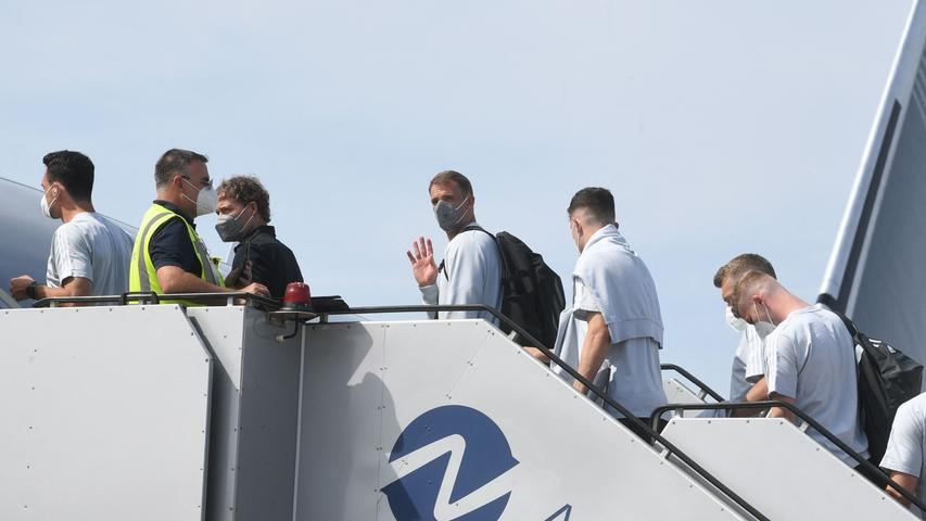 Germany's goalkeeper Manuel Neuer (C) waves while boarding a plane at Nuremberg Airport, on June 28, 2021, as Germany's team travel to the United Kingdom on the eve of their UEFA EURO 2020 football match against England, played at Wembley Stadium in London. (Photo by Christof STACHE / AFP)