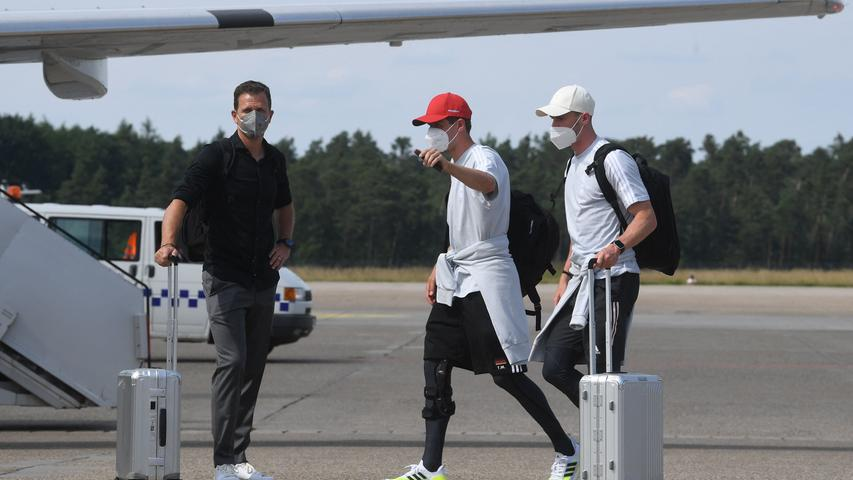 (L-R) Germany's sporting director Oliver Bierhoff, forward Thomas Mueller and defender Robin Gosens board a plane at Nuremberg Airport, on June 28, 2021, as Germany's team travel to the United Kingdom on the eve of their UEFA EURO 2020 football match against England, played at Wembley Stadium in London. (Photo by Christof STACHE / AFP)
