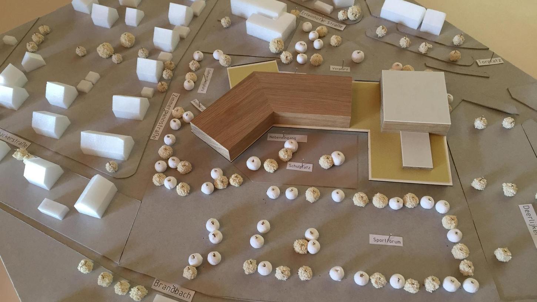 Das Modell der neuen Grundschule von Neunkirchen zeigt einen gewinkelten Baukörper. Im Hintergrund ist im Modell das benachbarte Feuerwehrhaus zu erkennen.