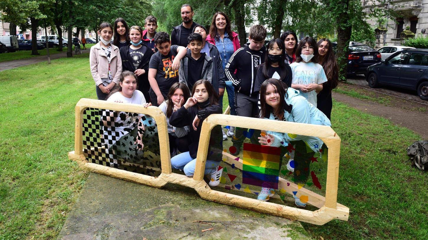 Nach getaner Arbeit versammelten sich die Schüler und Schülerinnen der 5 a der Otto-Seeling-Mittelschule mit ihrer Lehrerin Ines Rottammer und dem Künstler Sebastian Hertrich hinter der neu gestalteten Holzbrille.