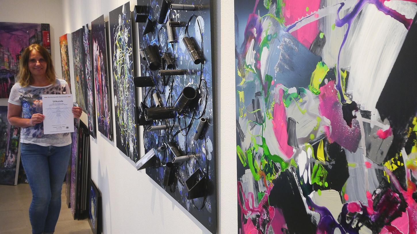 Sabine Weigand in ihrem Atelier in Abenberg vor einigen ihrer Bilder auf Carbonplatten. Für die innovative Technik hat sie den Gebrauchsmusterschutz, vereinfacht gesagtdas