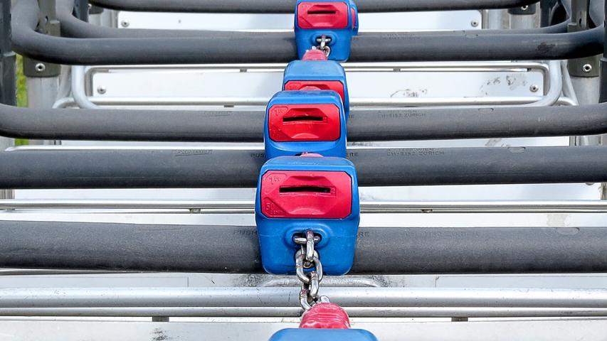 Aufgereiht und ineinander geschoben warten die Trolleys am Nürnberger Flughafen auf ihre Bestimmung. Die blau-rot hervorgehobenen Schlösser demonstrieren, dass die hilfreichen Kofferkulis