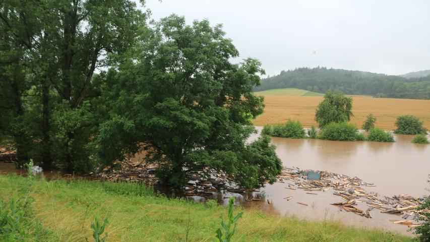 Die Wiese eines benachbarten Bauernhofs in Holzhausem, einem Ortsteil von Ipsheim, stand komplett unter Wasser. Berge von gelagertem Holz wurden weggespült.