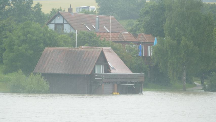 Ein Gebäude der Wasserwacht (vorne) am Obernzenner See in Obernzenn versank am Freitag im Wasser.