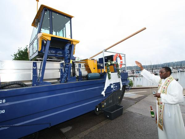 Bei einer Schiffstaufe darf die zerberstende Flasche Sekt ebenso wenig fehlen wie das Weihwasser, mit dem Pfarrvikar Patrick Okonkwo das Mähboot