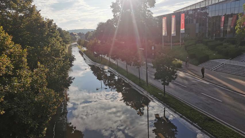 Am Brückencenter läuft das Wasser der Rezat bereits über die Straße. Die Kreuzung war am Abend für mehrere Stunden komplett gesperrt. Dadurch kam es zu einem größeren Verkehrschaos in Ansbach.