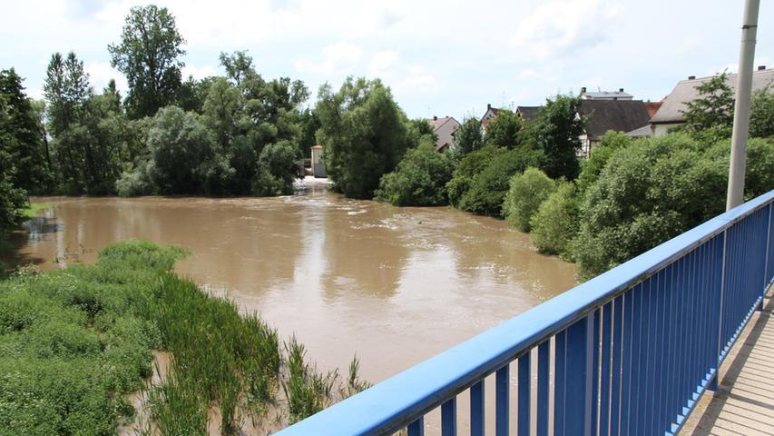 Die Aisch wälzt sich braun durch Hallerndorf.