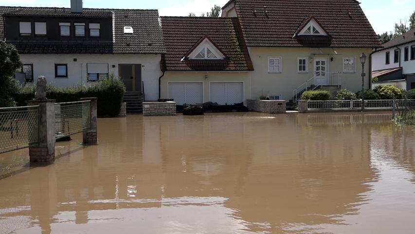 Gegen das Hochwasser kämpfen die Einsatzkräfte auch noch am Samstag (10.07.2021) in Höchstadt an der Aisch (Lkr. Erlangen-Höchstadt). Dort steht ein kompletter Park unter Wasser. Von einem Fahrgeschäft ist nur noch wenig zu sehen. Auch vor den Häusern steht das Wasser noch immer.