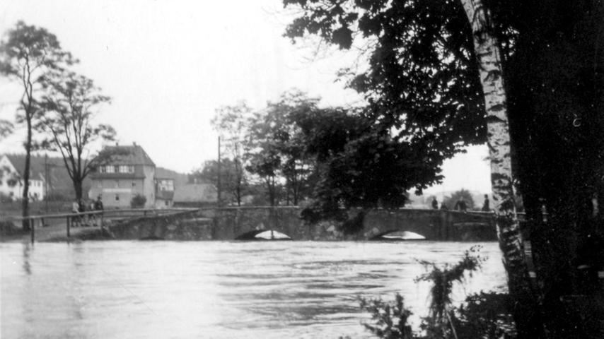 Nach tagelangem Regen war der Pegel der Aurach stark angestiegen. Ein im Talkessel der Nutzung niedergegangener Sturzregen verursachte den Bruch des Dammes am Wiwaweiher. Hier ist die Steinerne Brücke in Herzogenaurach zu sehen.