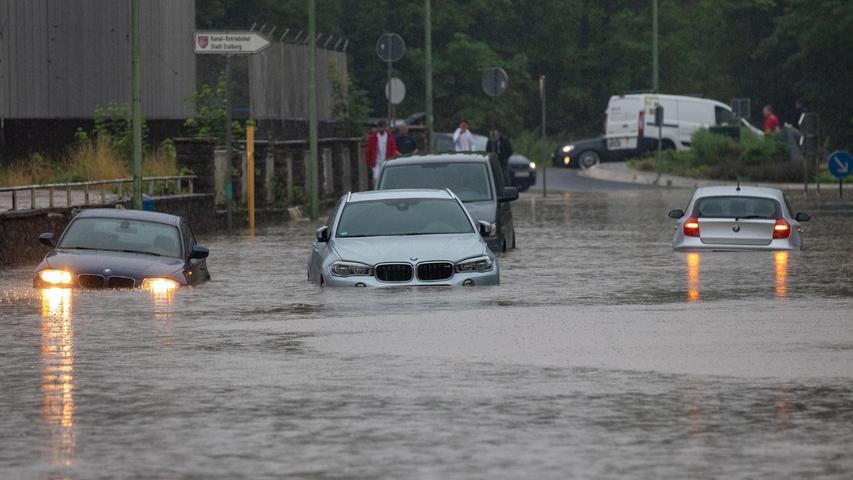Mehrere Autos stecken nach Starkregen auf einer überfluteten Straße in Stolberg bei Aachen fest.