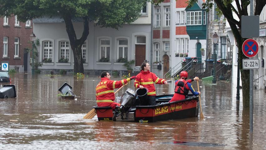 Ein Boot der Deutschen Lebens-Rettungs-Gesellschaft (DLRG) schlängelt sich durch Aachen - einige Straßen stehen komplett unter Wasser.