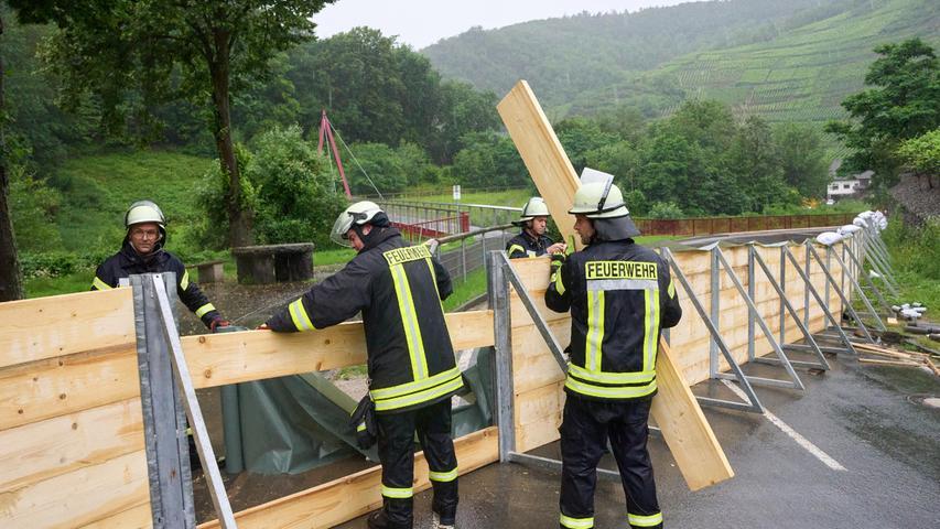 Feuerwehrleute haben im Ahrtal bei Mayschoss eine Sperrwand aus Holz errichtet, um zu verhindern, dass das Hochwasser der Ahr in den Ort läuft.